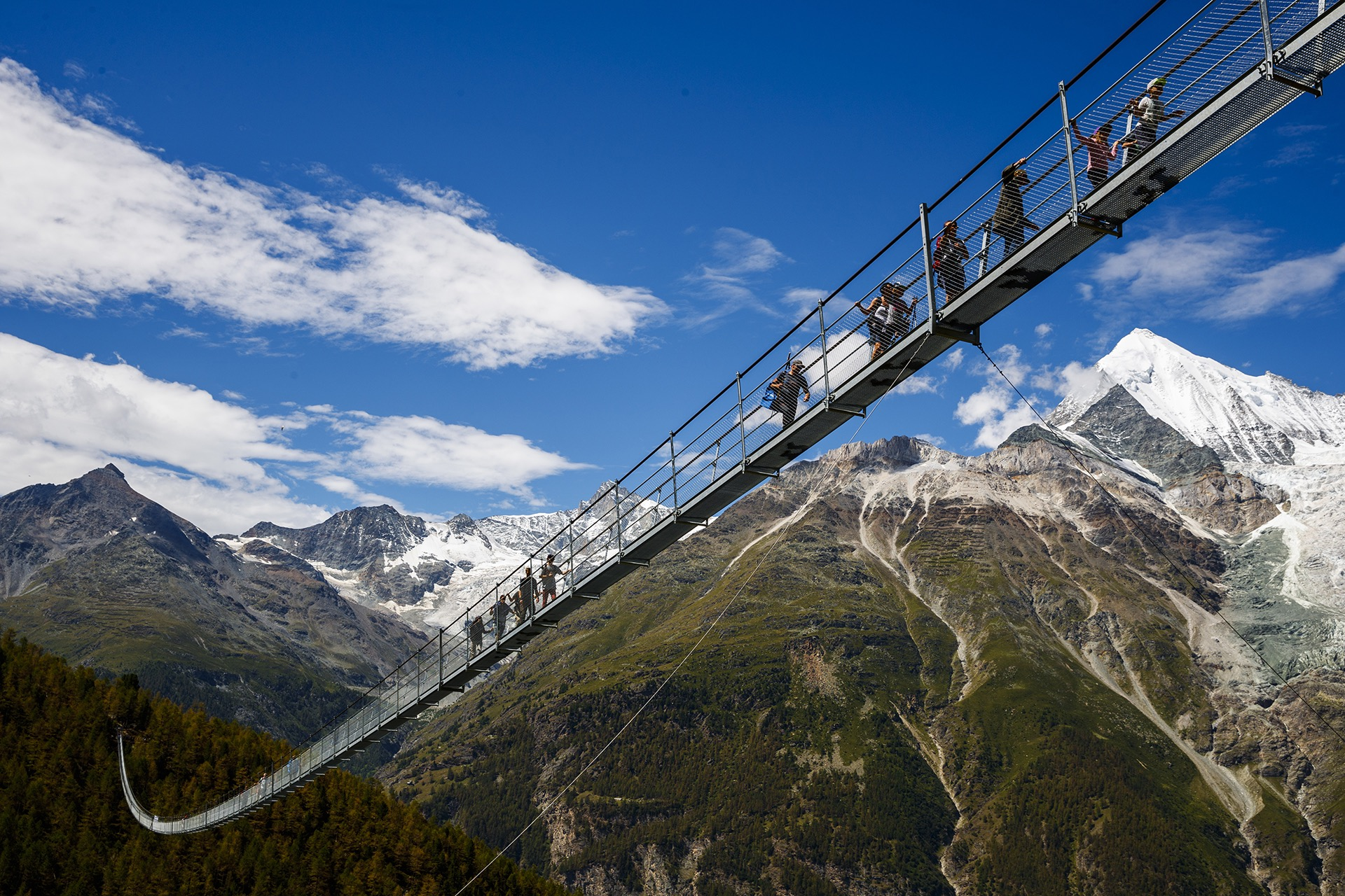 """People walk on the """"Europabruecke"""", that is supposed to be the world's longest pedestrian suspension bridge with a length of 494m, after the official inauguration of the construction in Randa, Switzerland, on Saturday, July 29, 2017. The bridge is situated on the Europaweg that connects the villages of Zermatt and Graechen. (Valentin Flauraud/Keystone via AP)"""